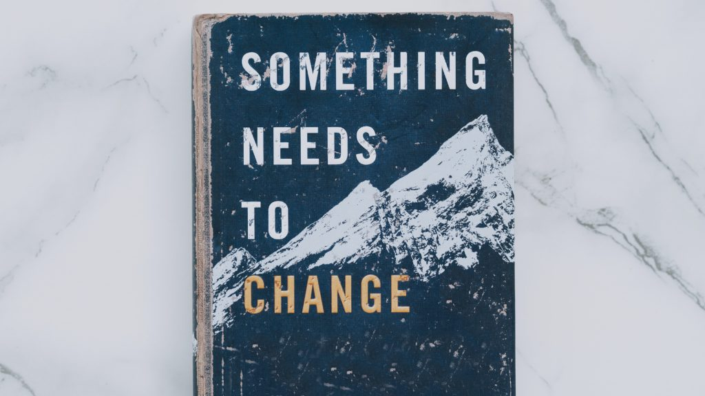 "Worn book cover title, ""Something Needs to Change"""